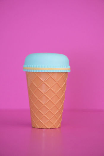 Close-up of coffee cup against pink background