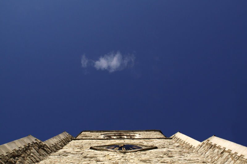 Low angle view of ruined building against blue sky
