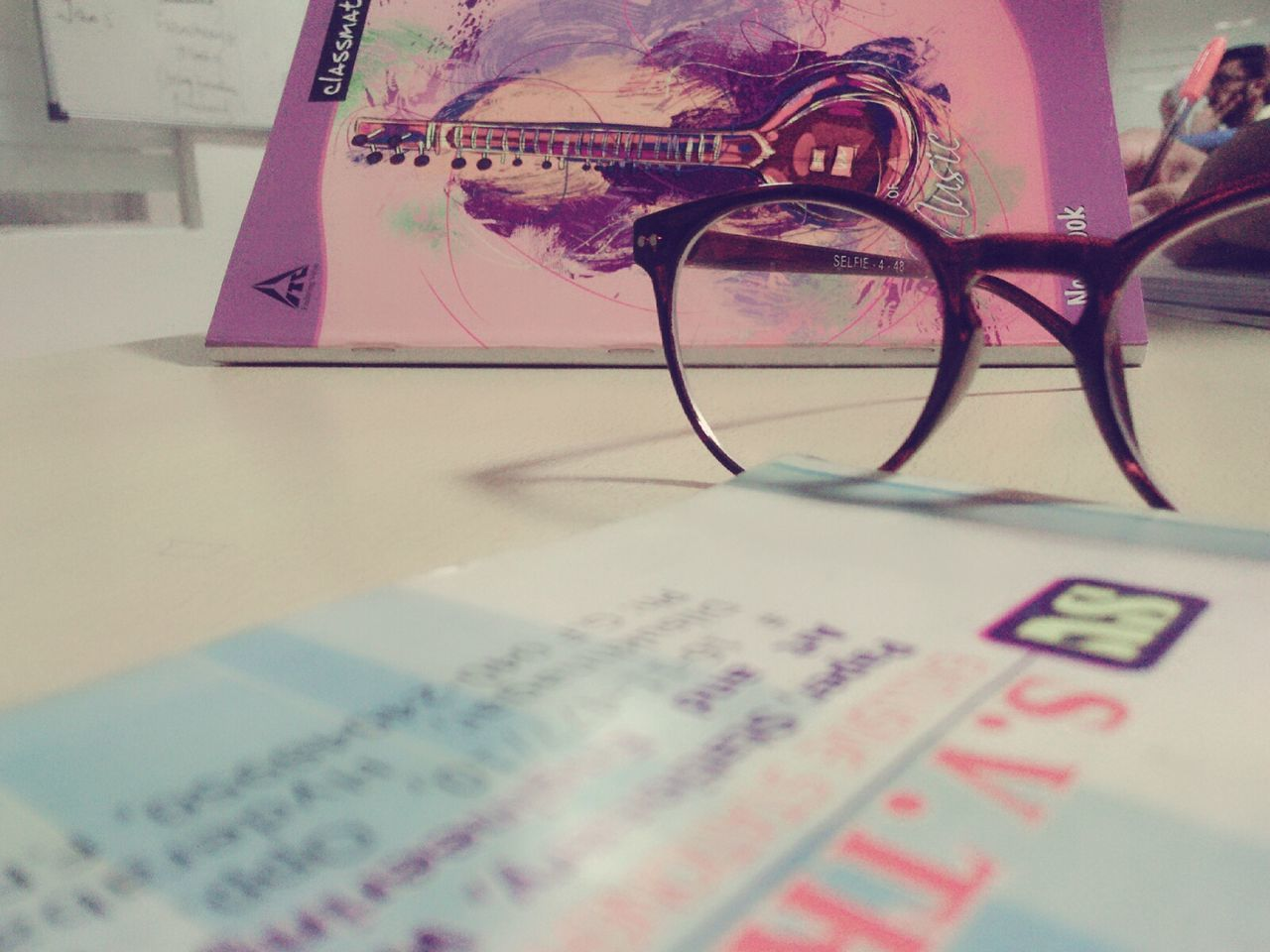 text, indoors, education, communication, book, magnifying glass, table, paper, no people, close-up, eyeglasses, day