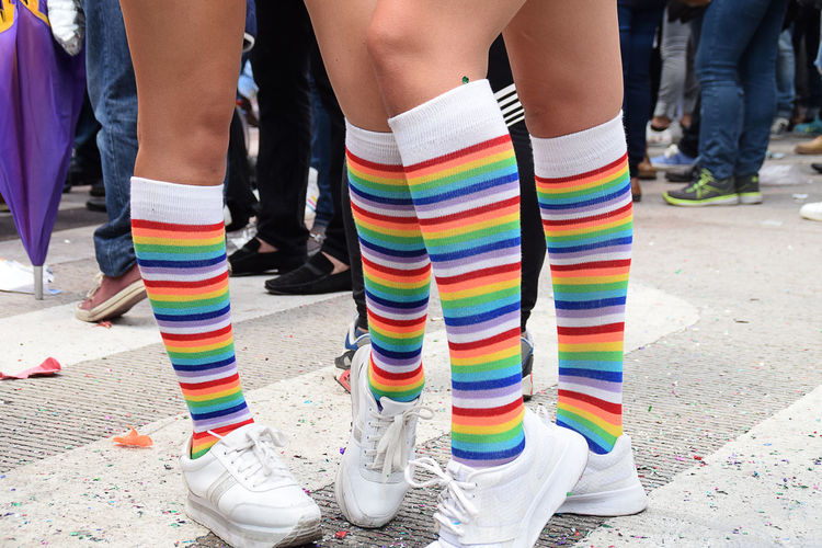 Low section of people wearing colorful socks while standing on street