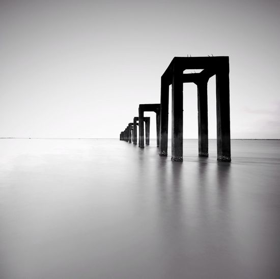 Fine art image in black & white of abandon jetty at Tumpat,  Kelantan. Malaysia. Soft focus due to long exposure. Kelantan Malaysia Fine Art Photography Blackandwhite Wallpaper Art Jetty City Water Business Finance And Industry Sky Standing Water