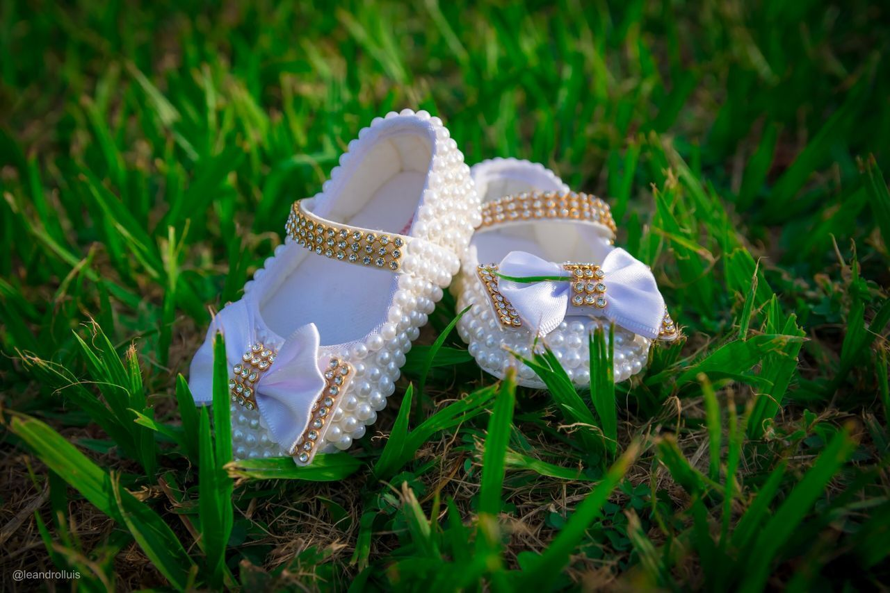 plant, grass, land, pair, field, no people, nature, close-up, shoe, green color, day, selective focus, growth, jewelry, outdoors, still life, white color, sandal, fashion, flower, personal accessory, womenswear