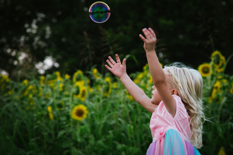 Arms Raised Blond Hair Bubble Child Childhood Day Focus On Foreground Human Body Part Leisure Activity Nature One Girl Only One Person Outdoors Real People Standing Sunflower Field