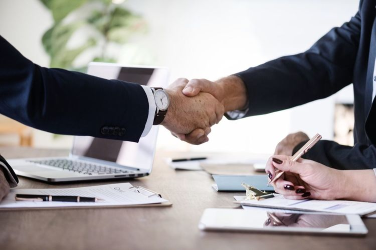 Cropped image of businessman shaking hands with male coworkers in office
