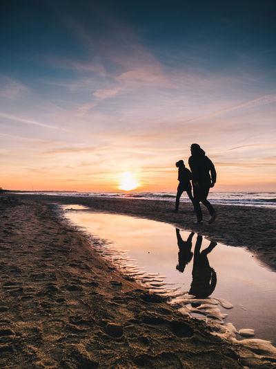 Silhouette Of Young Couple On Beach