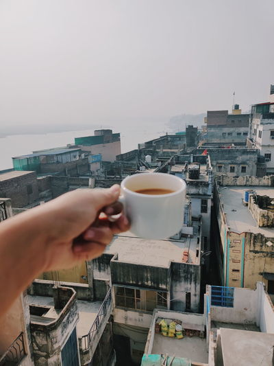 Man holding coffee cup and cityscape against sky
