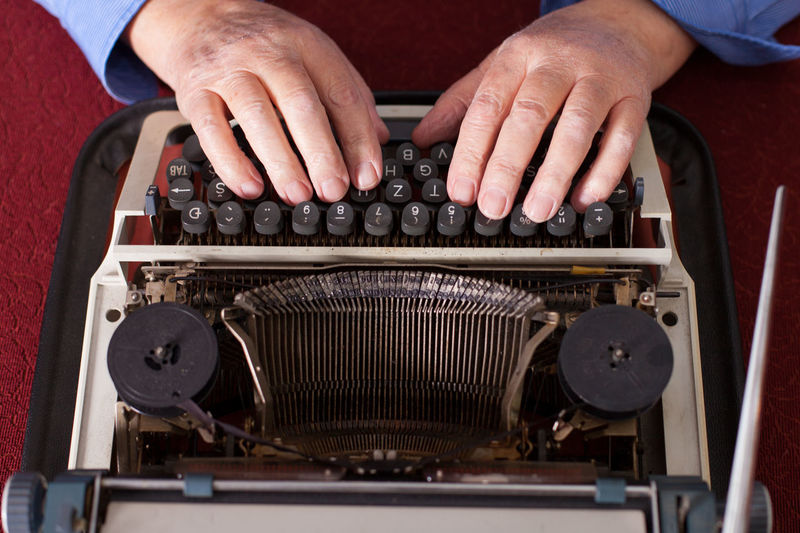 man writing on old typewriter Antique Author Close-up Detail Document Human Body Part Human Hand Indoors  Journalist Letter Man Novel Old Old-fashioned One Person Retro Story Table Typescript Typewriter Typing Vintage Work Wrinkled Writing