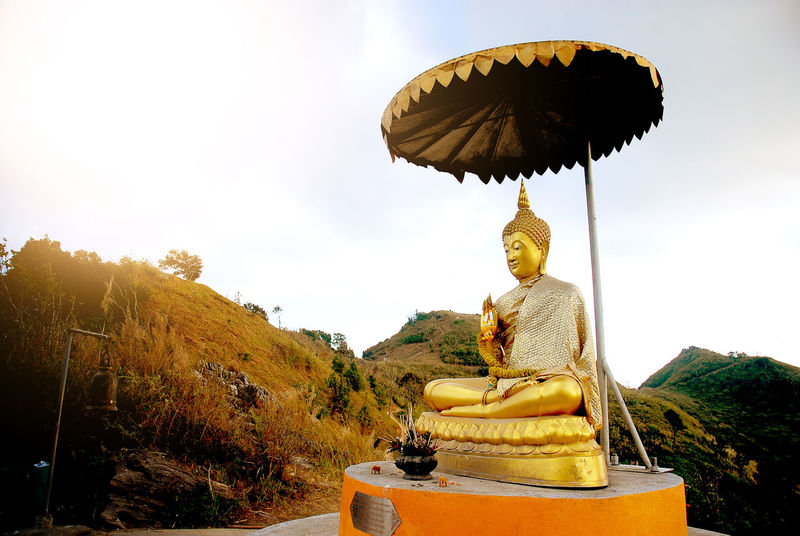 Buddha Cultures Day Gold Gold Colored Idol Mountain No People Outdoors Place Of Worship Religion Spirituality Statue Sun Light