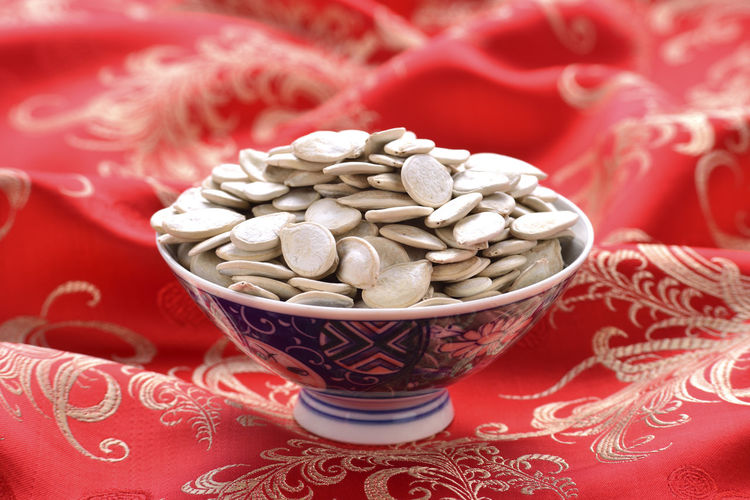 Nut snacks New Year Seed Bite Bowl Chinese New Year Close-up Day Dried Fruit Food Food And Drink Freshness Granules Health Healthy Eating Indoors  Melon Seeds No People Nut Nutrition Pumpkin Seeds Red Snacks