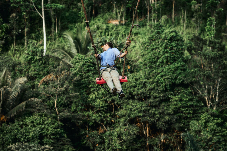 Man standing on rope in forest