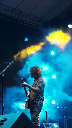 Side view of musician playing guitar during music festival