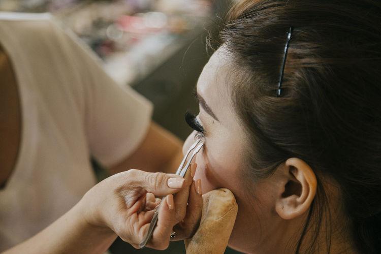 Make-up artist applying false eyelashes on young woman