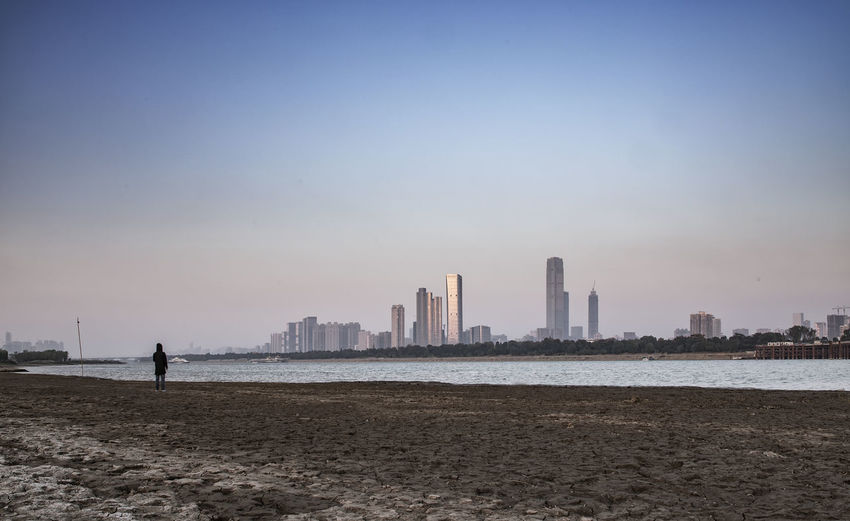 lonely city Architecture Beach Beauty In Nature Building Exterior Built Structure City Cityscape Clear Sky Day Men Modern Nature One Person Outdoors Real People Sand Sea Sky Skyscraper Standing Sunset Tourism Travel Destinations Urban Skyline Water