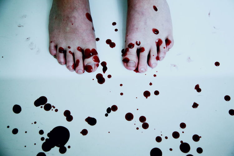 Low section of person with blood on floor