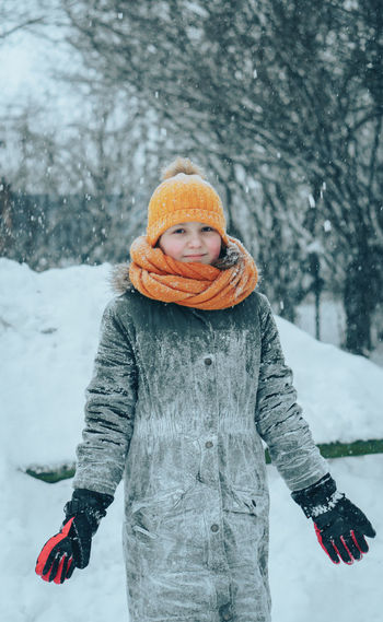 Portrait of girl standing on snow covered land