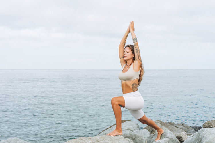 Young woman in white sport clothes practice yoga on sea beach, mental and phisical health