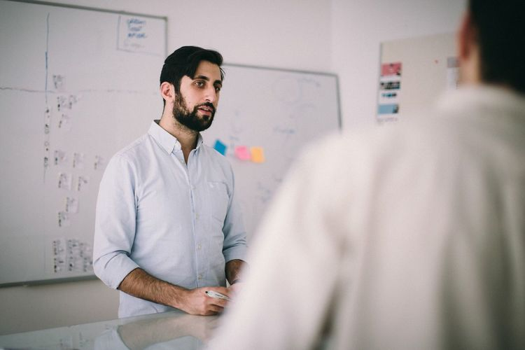 Real People Occupation Indoors  Standing Men Healthcare And Medicine Young Men Communication Selective Focus Beard Waist Up Young Adult People Adult Lab Coat Facial Hair Focus On Background Males  Expertise