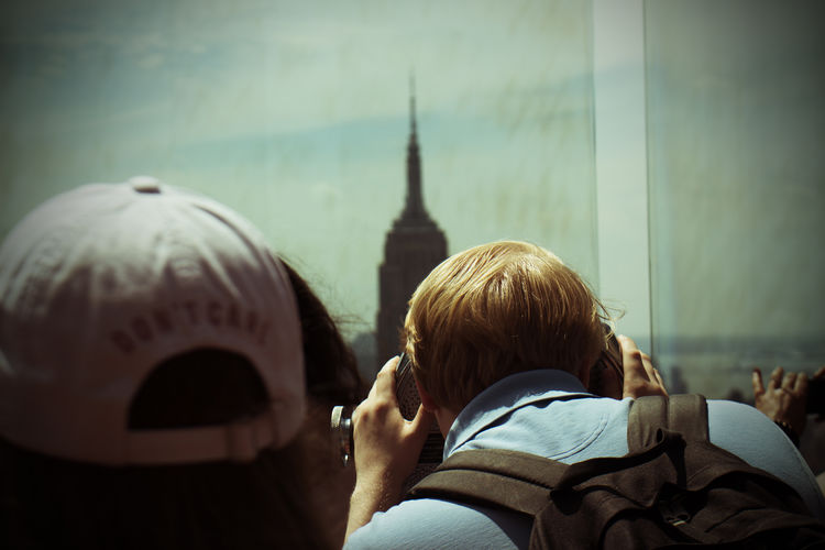 Rear view of people in front of empire state building in city