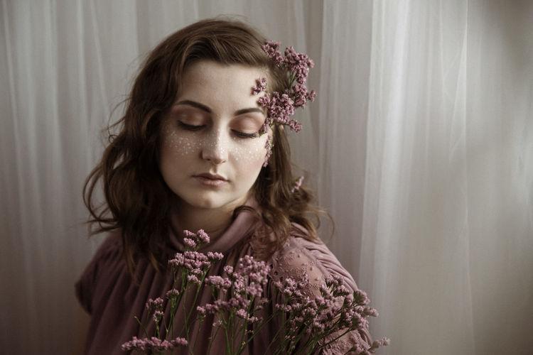 Woman wearing flowers looking down against curtain