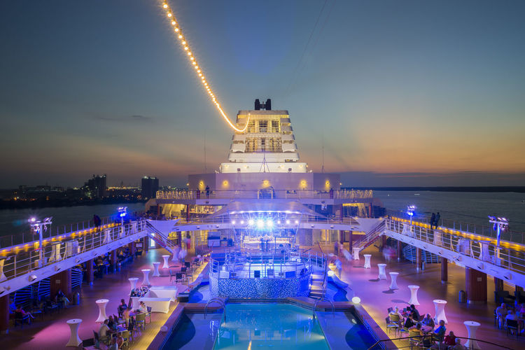 View of front deck of cruise ship sailing during sunset Harbor Holiday Transportation Blue Building Exterior Built Structure City Connection Criuse Crowd Deck Energy Illuminated Large Group Of People Malaysia Night Outdoors Platform Shipyard Sky Tourism Travel Destination Travel Destinations Vessel Water