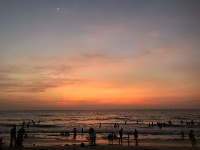 Group of people on beach during sunset