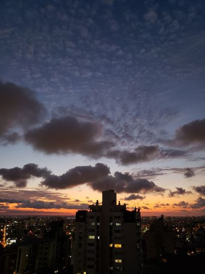 Silhouette buildings against sky at sunset