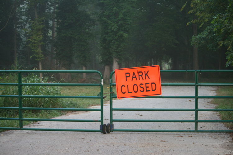 Locked Park Closed Road Wooded Area Communication Day Green Gate Locked Gate Nature No Entrance No People Orange Sign Outdoors Text Tree Wheels