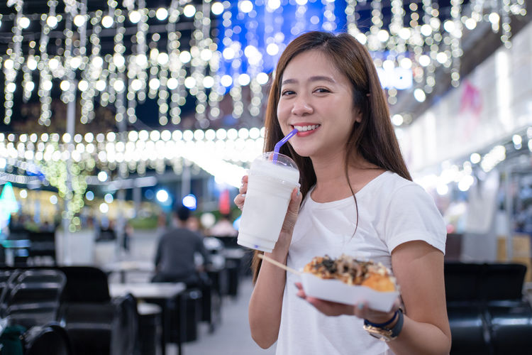 Portrait of woman eating food at night outdoors