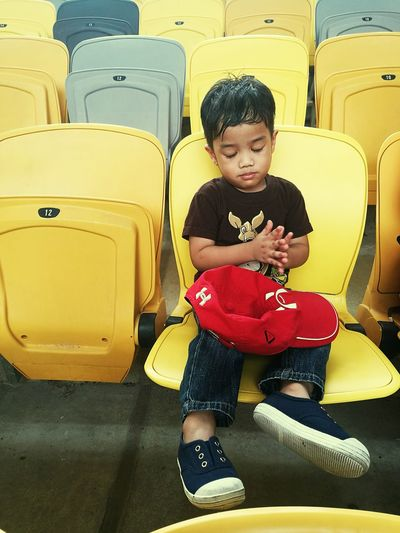 Paint The Town Yellow Childhood One Person Sitting Front View Casual Clothing Full Length One Boy Only Child Yellow Stadium Seating Sleepy Head CaptureTheMoment Cap