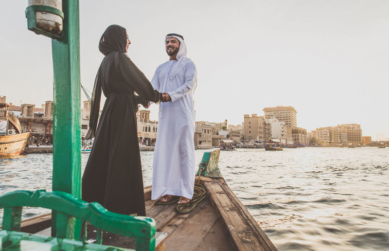 Cheerful couple holding hands while standing in boat on river at sunset