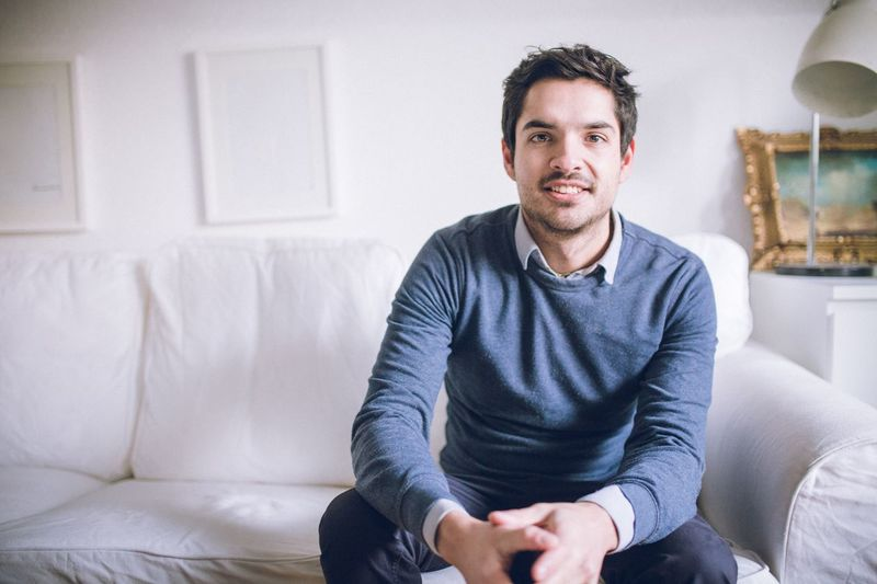 Portrait Looking At Camera Sofa Sitting One Person Indoors  Smiling Casual Clothing Confidence  Real People Lifestyles Living Room Happiness Front View Handsome Cheerful Day Architecture One Man Only