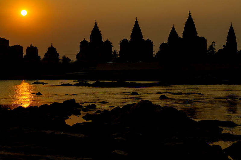 Silhouette of temple and cenotaphs at sunset by Betwa river, Orchha, India. Architecture ASIA Incredible India India Pagoda Place Of Worship Reflection Religion River Silhouette Sunset