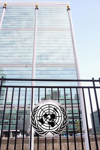 New York, USA - 26 September 2016: The United Nations Headquarters Building viewed through the fence with UN Logo - located on First Avenue, Manhattan. 1st Avenue Exterior Global Warming Peace Peace Keeping Politics United Nations Architecture Building Exterior Day Fence First Avenue Low Angle View No People Outdoors Sky United Nations Building World Politics