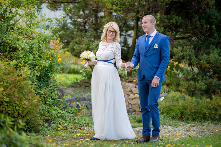 Bridal couple holding hands while standing at park