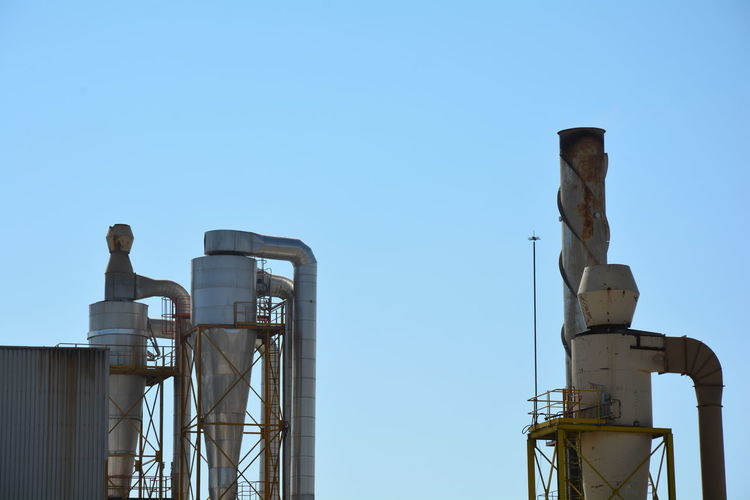 Chimney against clear blue sky at factory