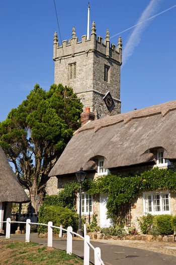 Village scene at Godshill Isle of Wight showing thatched cottages in front of the large church tower Godshill Home Quaint  Tourist Architecture Attraction Belief Blue Building Clear Sky Cottage Hillside History House Picturesque Place Of Worship Pretty Religion Stone Thatched The Past Tower Travel Destinations Tree Village