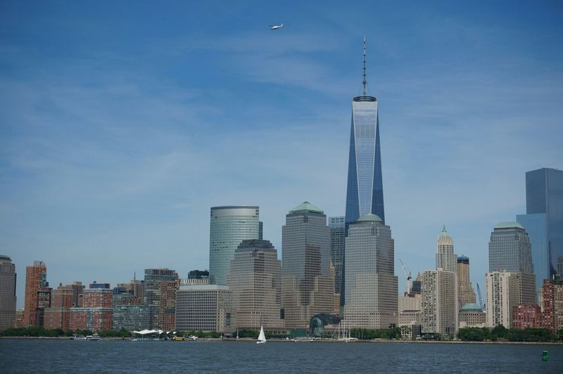 One world trade center by modern buildings against sky