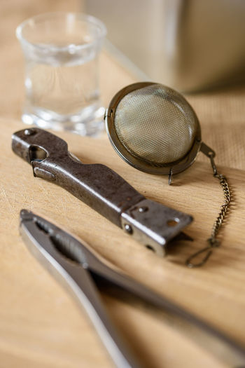High angle view of pliers and tea strainer on wooden table
