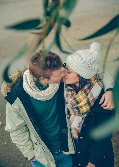 Couple embracing while wearing warm clothing in city