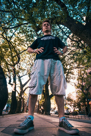 Low angle view of young man against trees