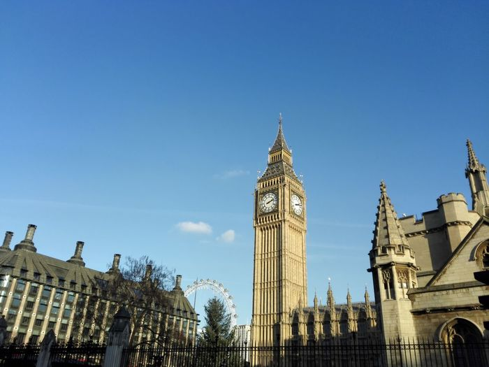 Low angle view of big ben and buildings against blue sky