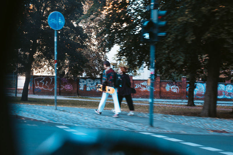 Man and woman walking on street by trees