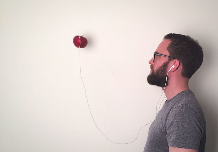 Side View Of Man With Headphones Attached To Apple On White Wall