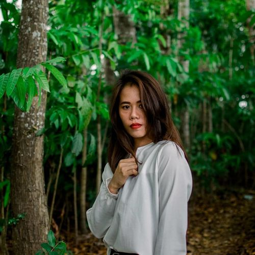 Portrait of woman standing against plants in forest