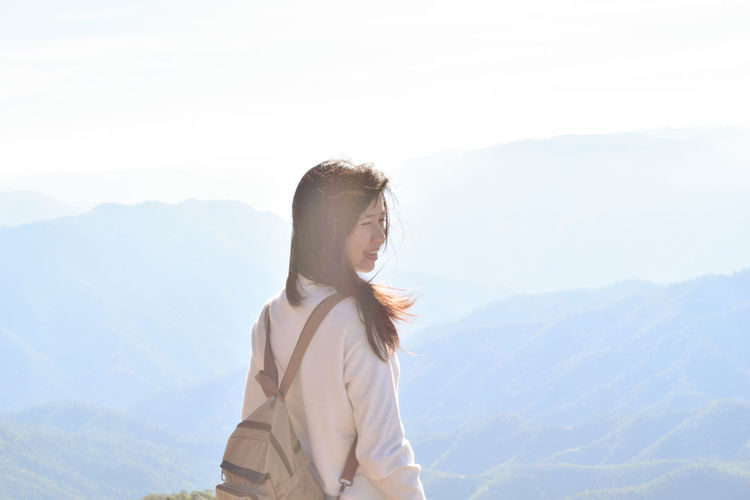 Smiling woman looking away while standing against mountains and sky