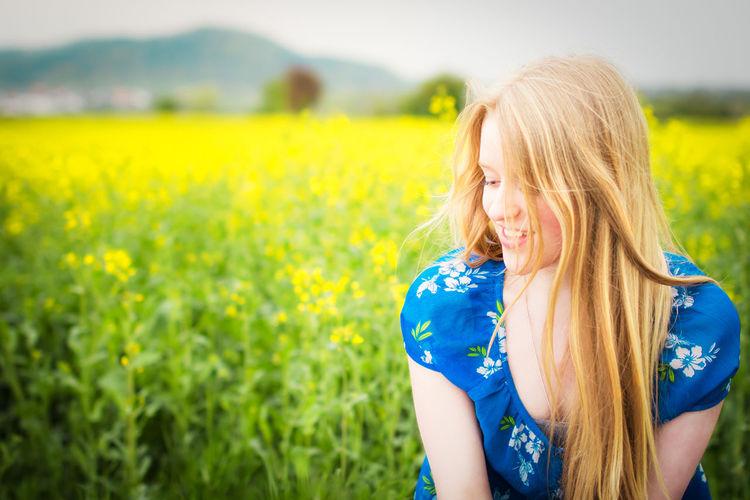 Smiling beautiful woman looking down against oilseed rape field