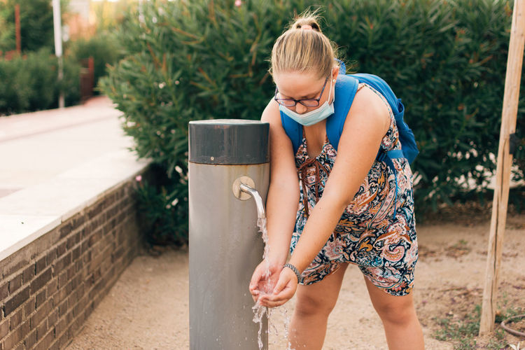 Chubby girl with face mask drinking water from the fountain