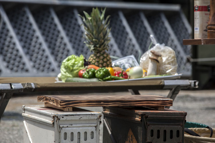 Cutting board on metal containers by fruits and vegetables on table during camping