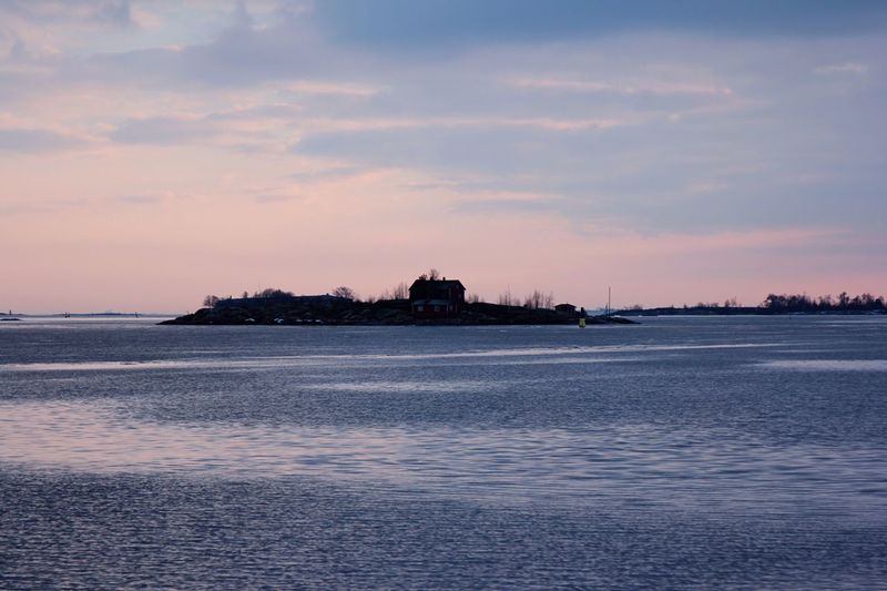 Hill In Baltic Sea Against Cloudy Sky During Sunset