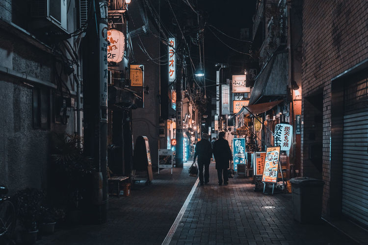 People walking on illuminated street amidst buildings in city at night